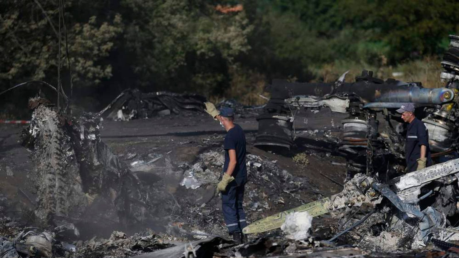 Members of the Ukrainian Emergencies Ministry work at the crash site of Malaysia Airlines Flight MH17 near the village of Hrabove, Donetsk region