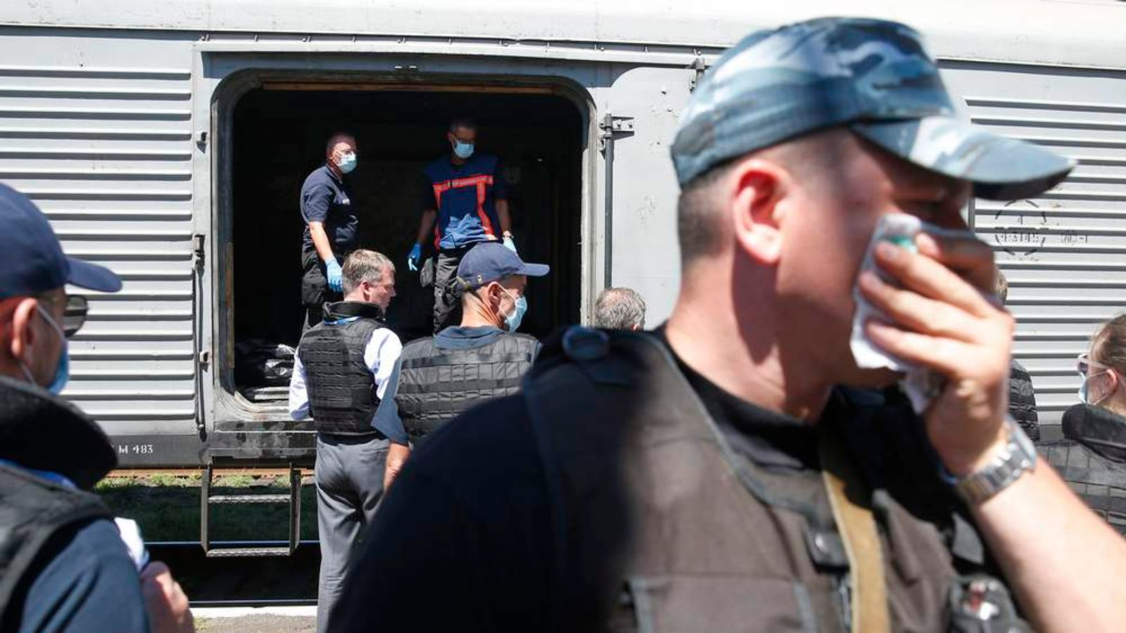 People surround a refrigerator wagon at a railway station in the eastern Ukrainian town of Torez