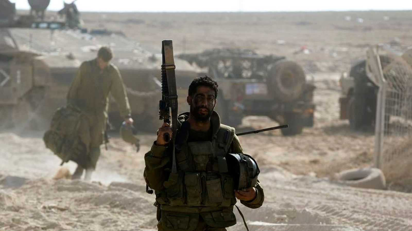 An Israeli soldier carries a weapon near the border with the Gaza Strip