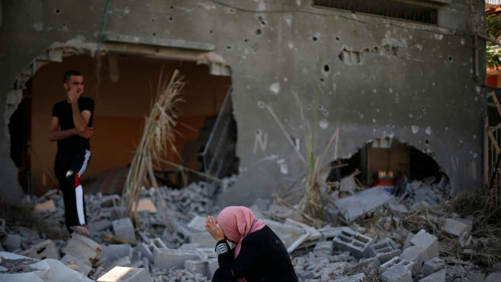 A Palestinian woman reacts upon seeing her destroyed house in Beit Hanoun town