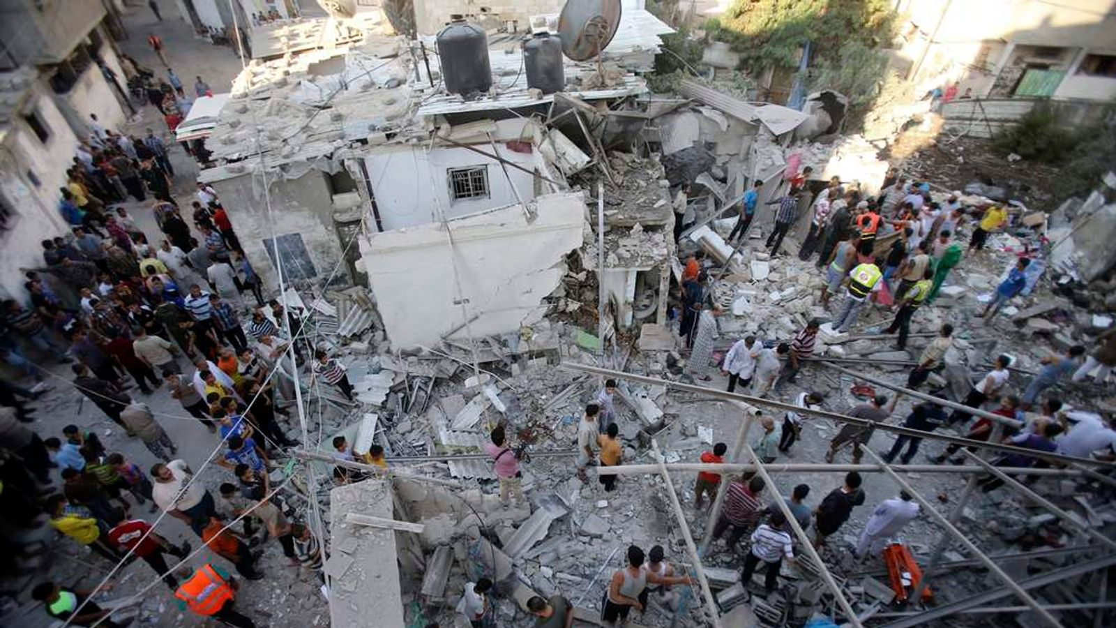 Rescue workers search for victims as Palestinians gather around the wreckage of a house in Rafah.