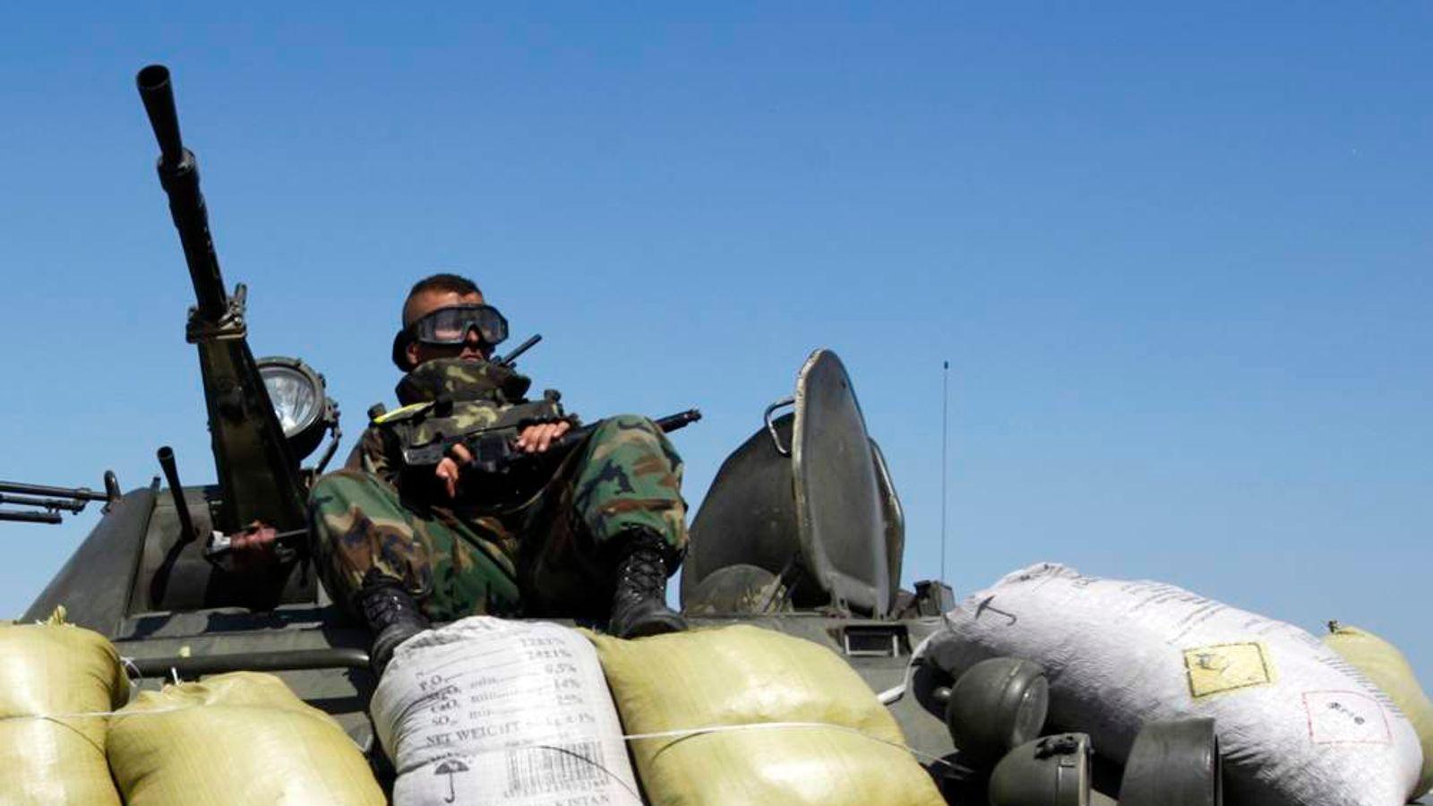 A Ukrainian serviceman sits on a military armoured vehicle near Donetsk