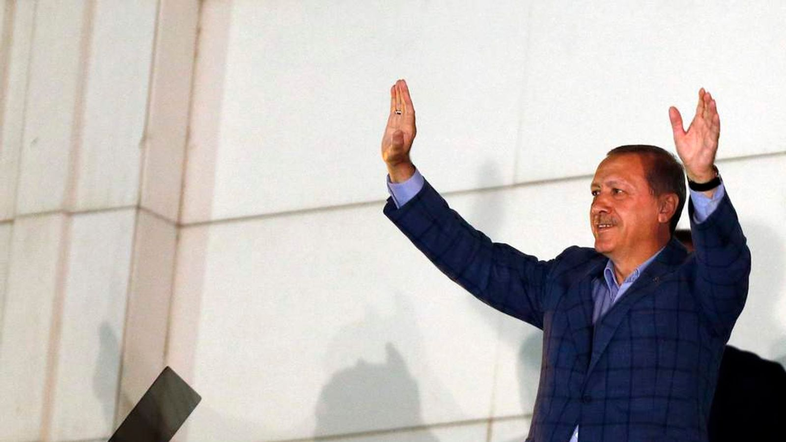 Turkey's Prime Minister Erdogan waves hands as he celebrates his election victory in front of the party headquarters in Ankara