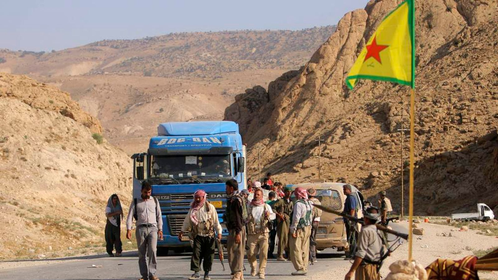 Yazidi fighters who recently joined the Kurdish People's Protection Units  secure a road in Mount Sinjar