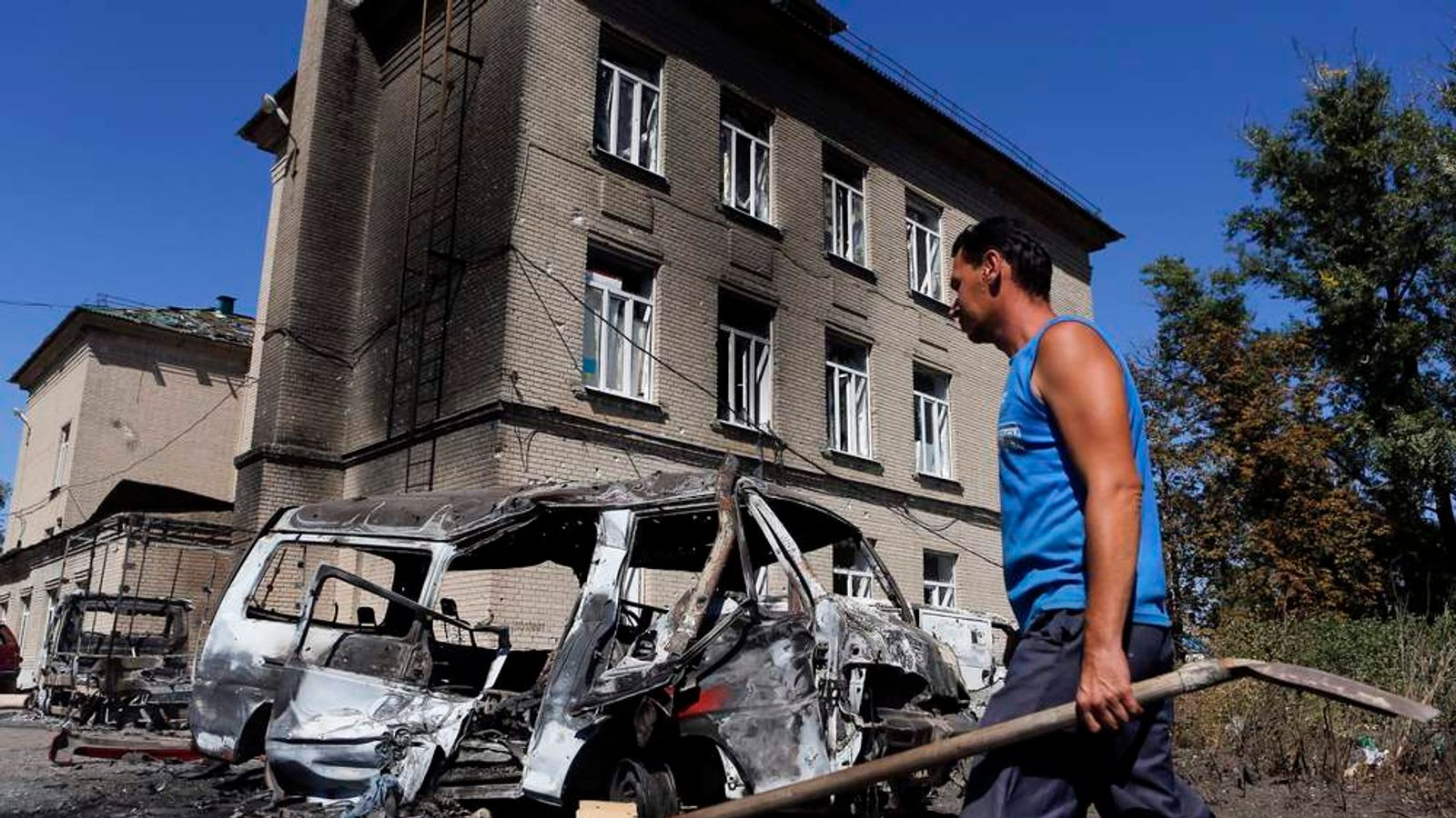 A man walks past vehicles destroyed during the recent shelling in the eastern Ukrainian town of Ilovaysk