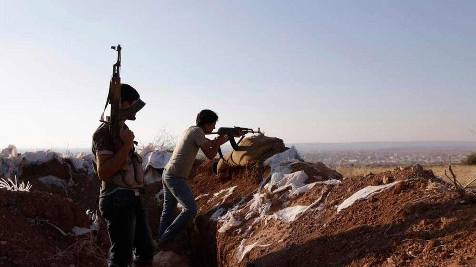 Armed Free Syrian Army fighters stand on one of the frontlines of Wadi Al-Dayf camp in the southern Idlib countryside