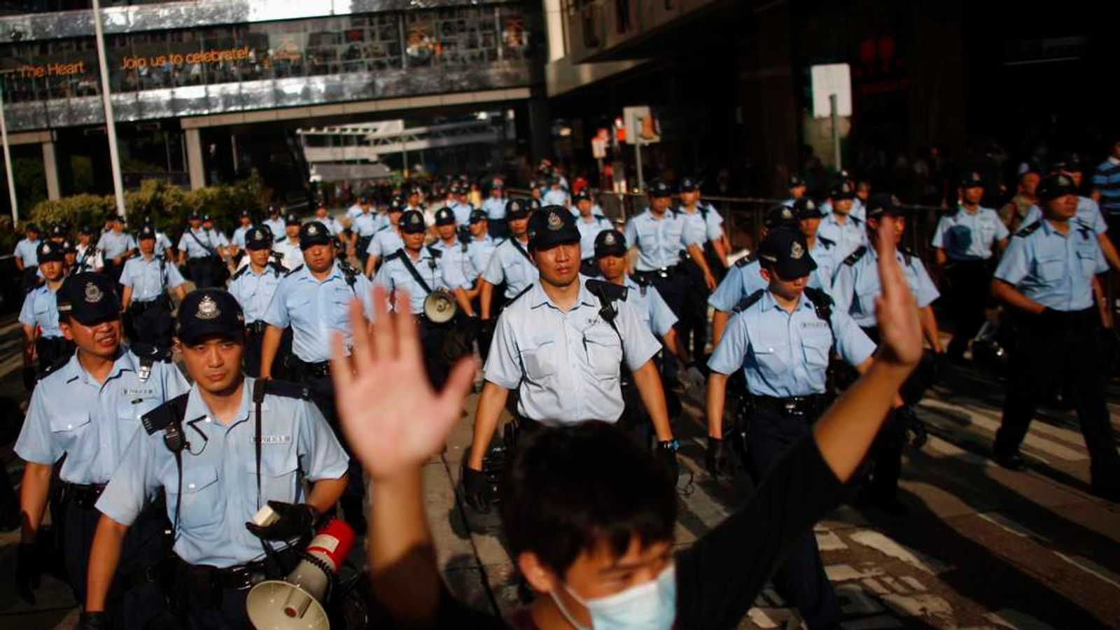 A protester raises his arms as police officers try to disperse the crowd near the government headquarters in Hong Kong