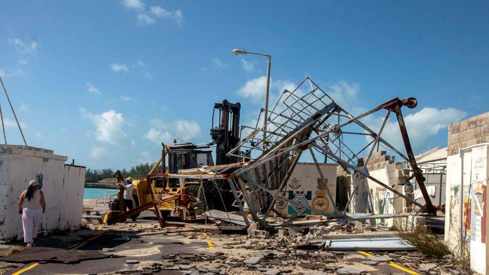 Woman walks around debris after Hurricane Gonzalo