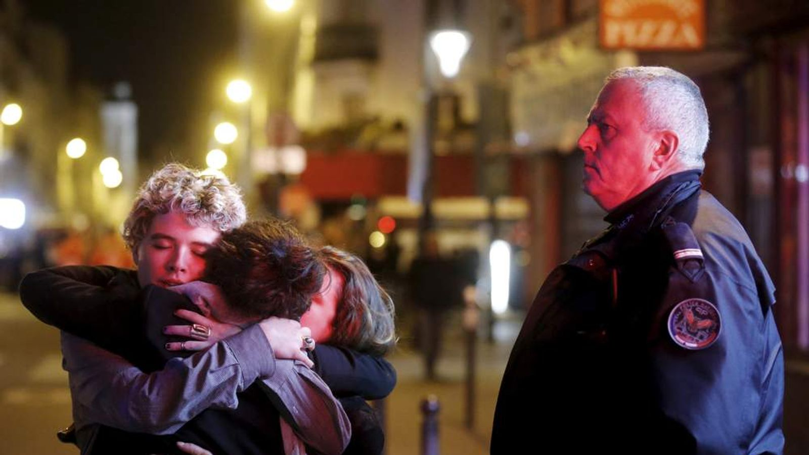 People hug on the street near the Bataclan concert hall following fatal attacks in Paris, France