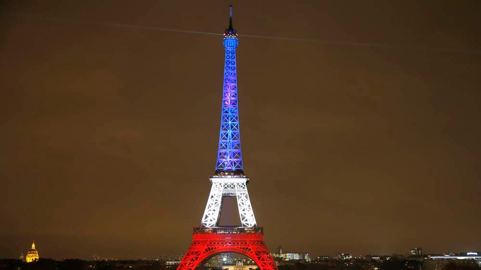 The Eiffel Tower is lit with the blue, white and red colours of the French flag in Paris to pay tribute to the victims of a series of deadly attacks on Friday in the French capital