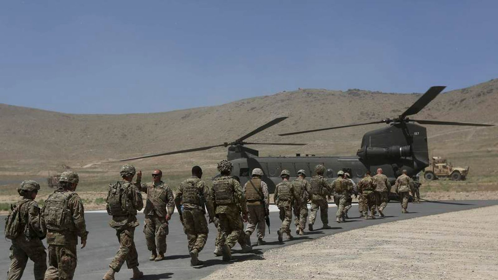 NATO soldiers board Chinook helicopter after a security handover ceremony at a military academy outside Kabul