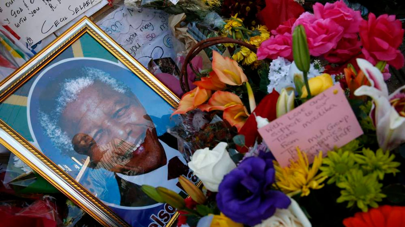 A well-wisher is reflected in a glass outside the hospital where Mandela is being treated in Pretoria