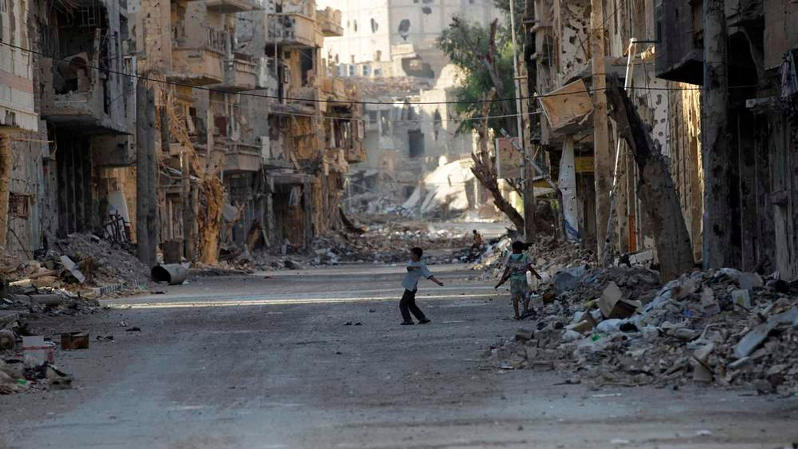 Syrian children play in a damaged street in Deir al-Zor