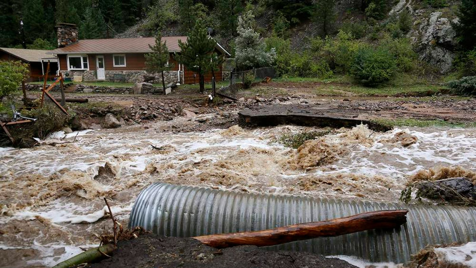 A home is stranded after a flash flood in Coal Creek destroyed the bridge near Golden