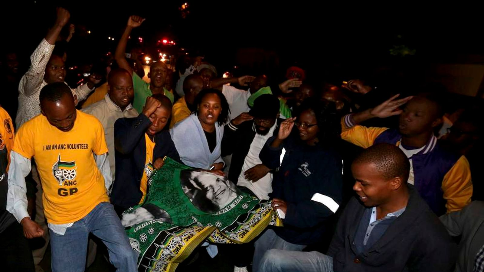 People chant slogans outside the house of former South African President Mandela after news of his death in Houghton