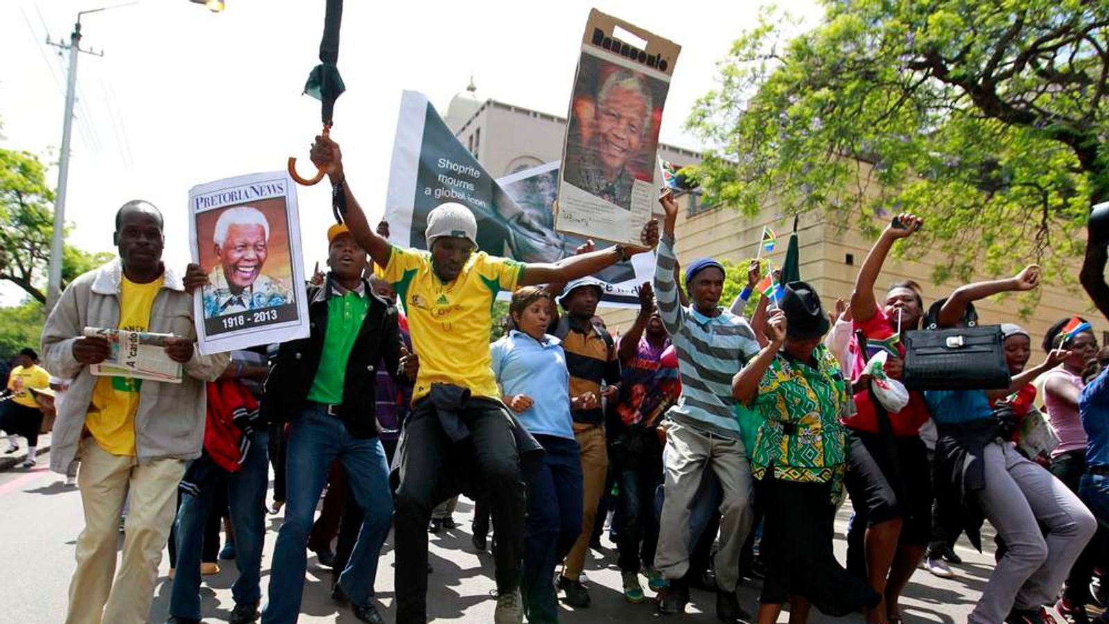 People chant slogans and dance as they prepare to view the body of former South African President Nelson Mandela as it lies in state, outside the Union Buildings in Pretoria