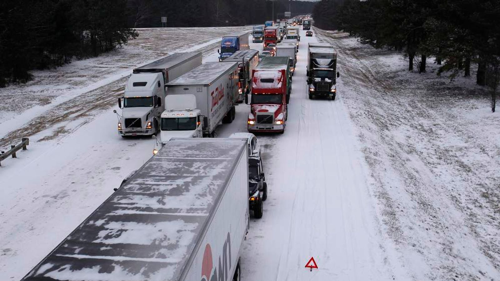 Cars and trucks are gridlocked on I-75 interstate highway after a rare snowstorm in Kennesaw