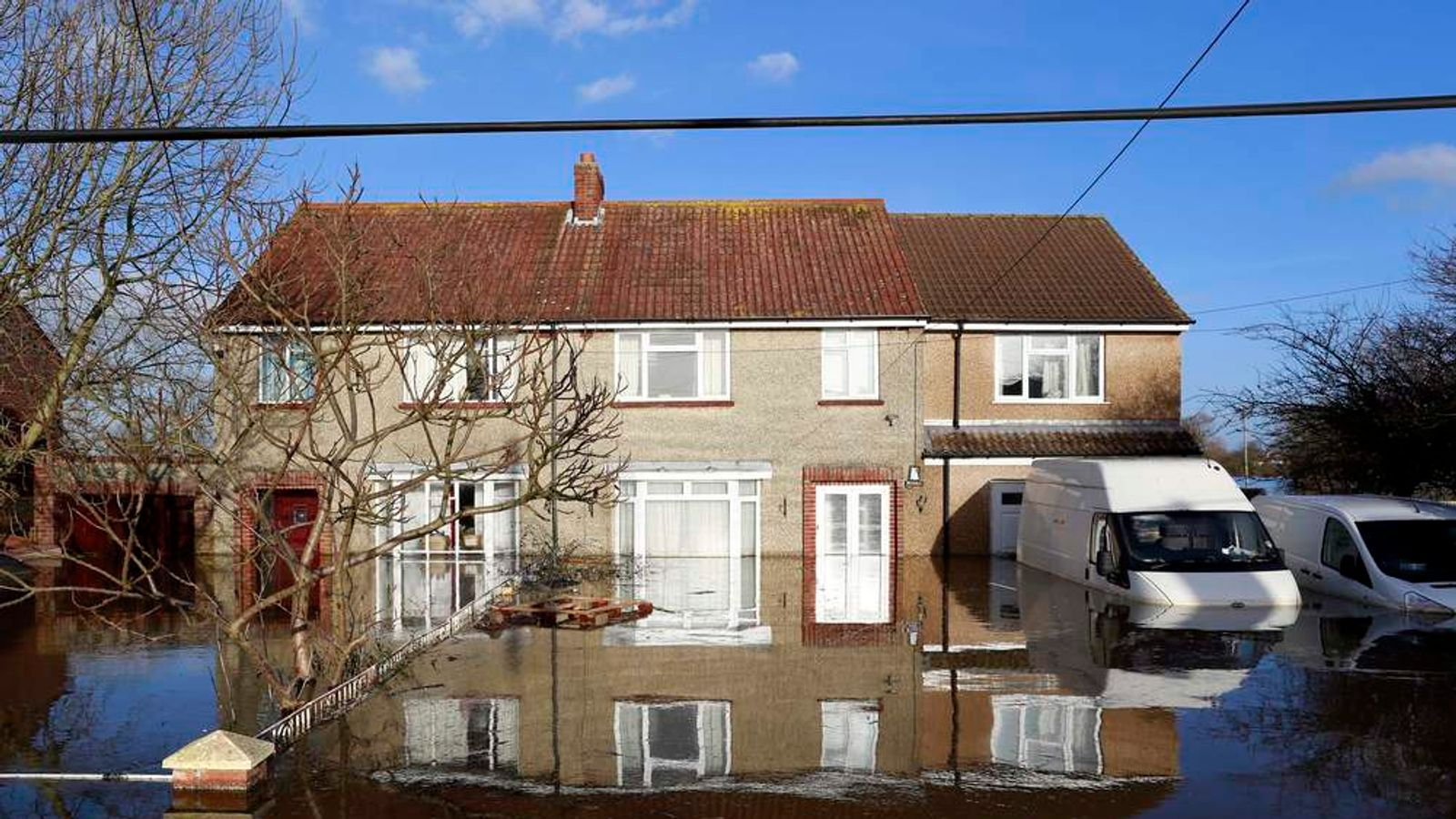 Stranded vehicles are seen in urban landscape taken in the flooded Somerset village of Moorland