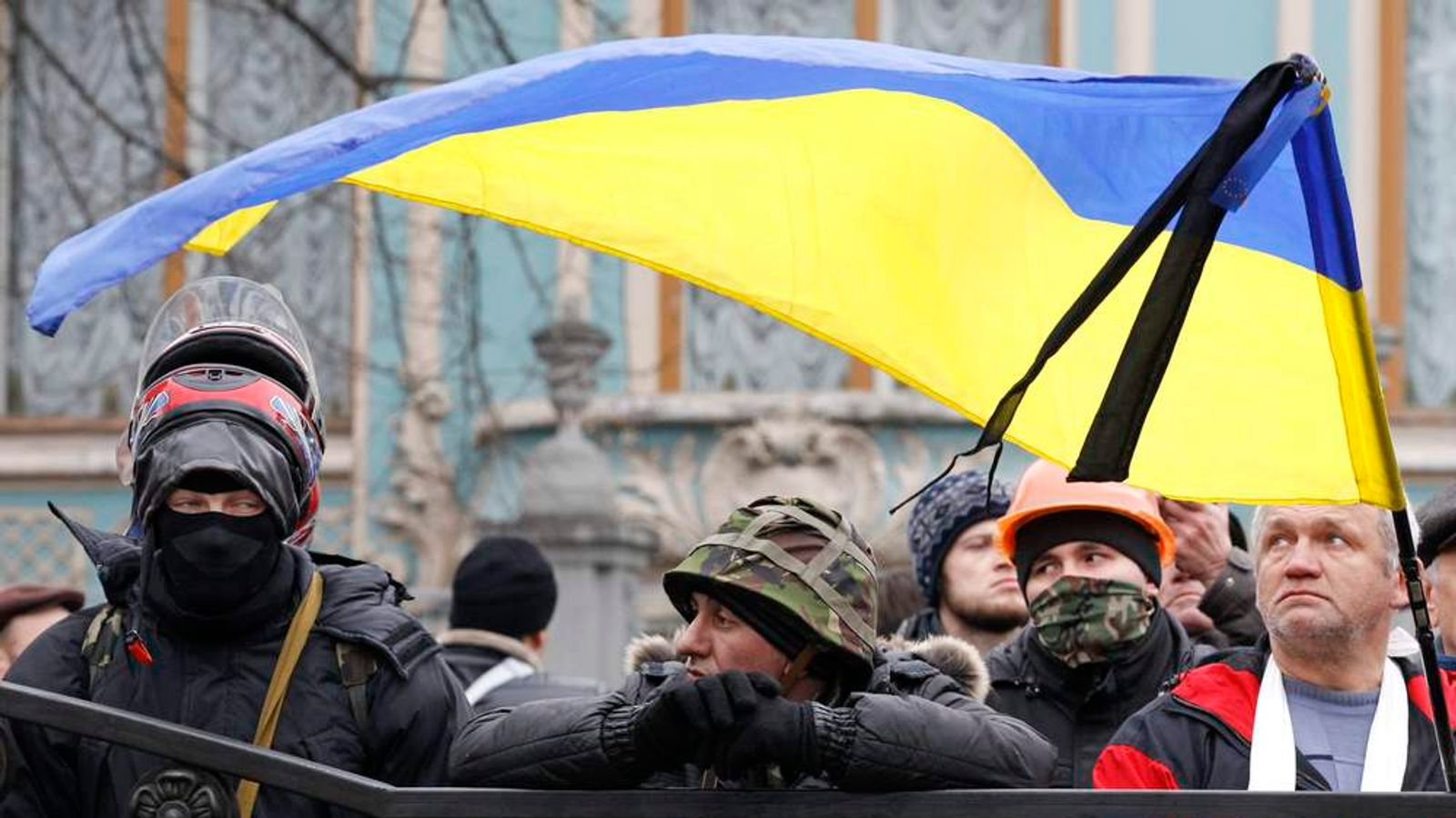 Anti-government protesters gather outside the Ukrainian Parliament building, with a black ribbon attached to a Ukrainian national flag to mark a day of mourning for the victims of clashes, in Kiev