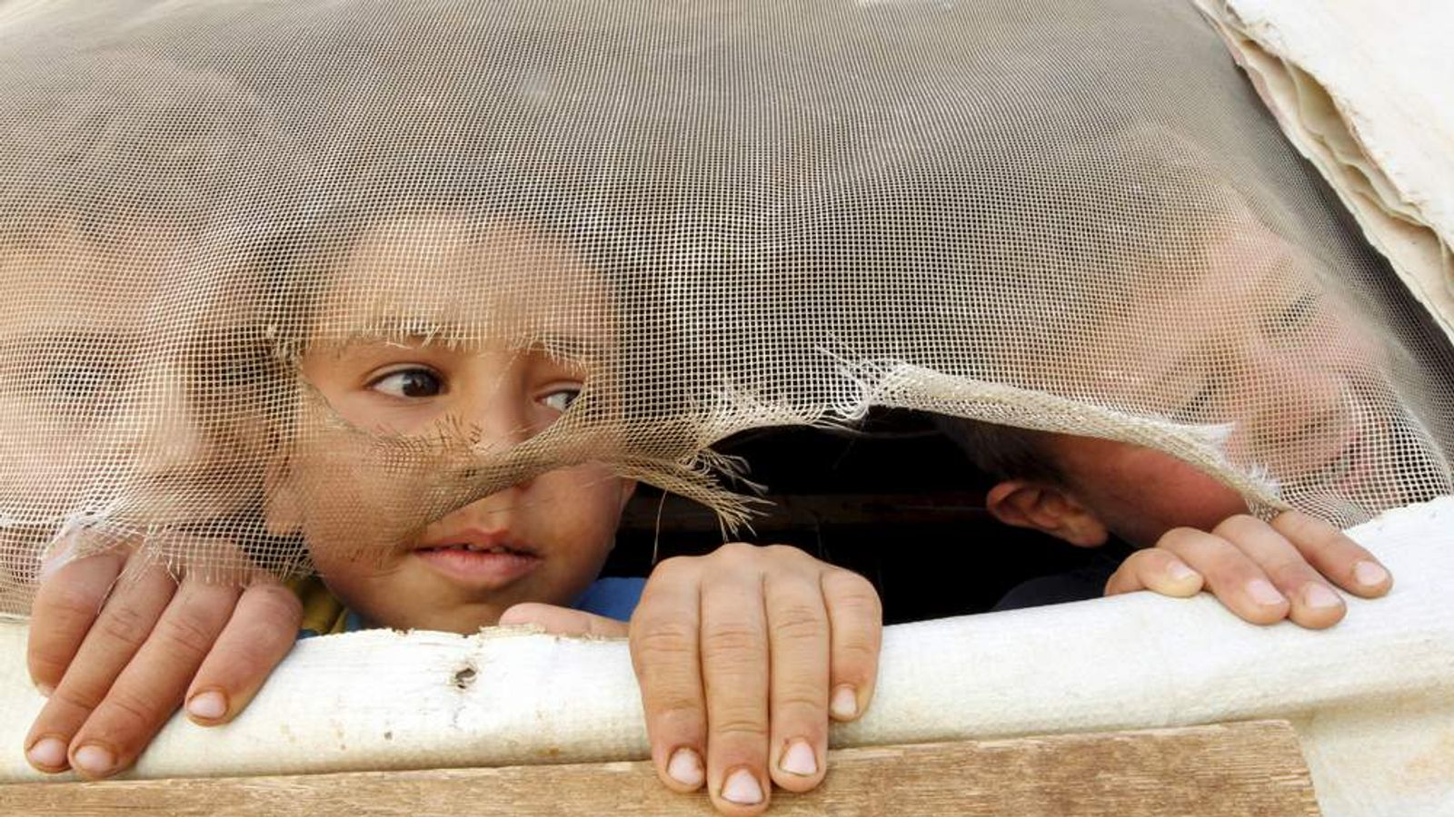 Syrian refugee children look out from their tent during a visit by U.N. Humanitarian Chief and Emergency Relief Coordinator O'Brien to their makeshift settlement in Saadnayel in Lebanon's Bekaa Valley