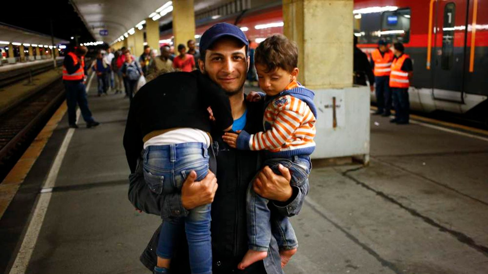 A migrant carries his children at the railway station in Vienna