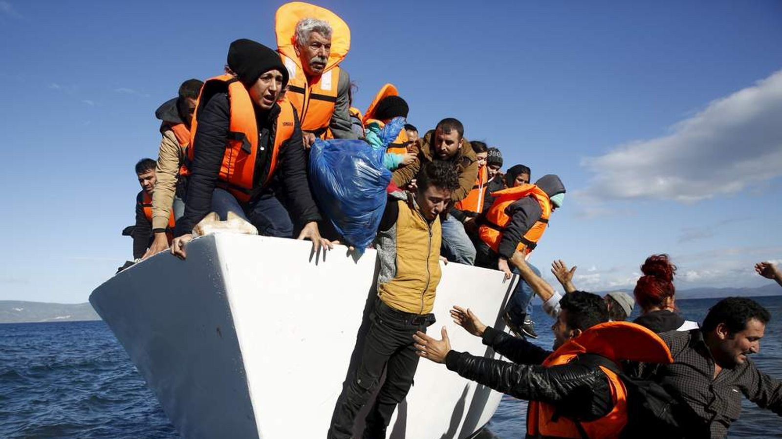 Refugees and migrants jump off a boat as they arrive on the Greek island of Lesbos