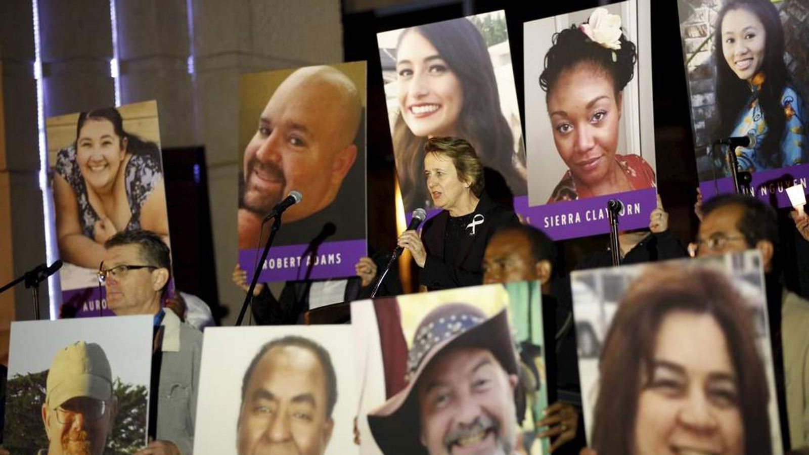 Mary Kay Henry, international president of the SEIU, speaks while surrounded by photos of the 14 people killed during a vigil for San Bernardino County employees after last week's shooting in San Bernardino, California