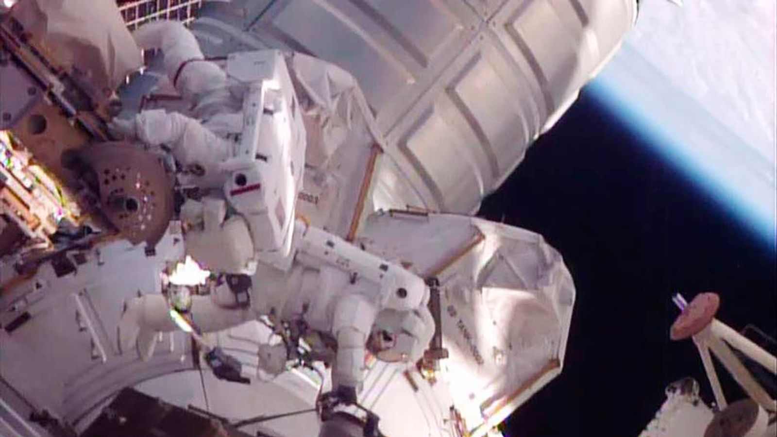 NASA astronauts work to move a stalled robotic transporter on International Space Station in this still image from NASA TV.