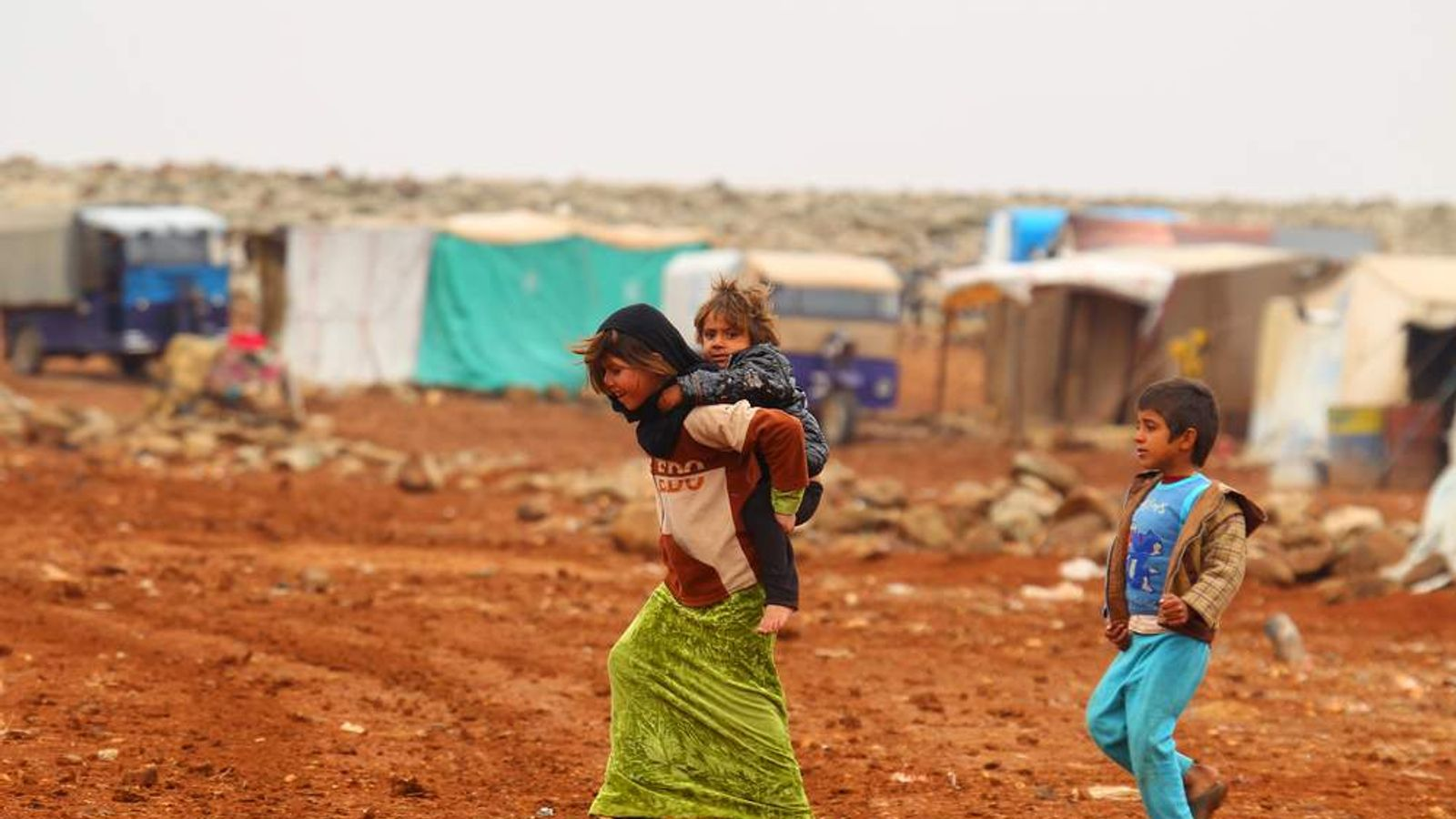 An Internally displaced Syrian youth carries a baby on her back inside a refugee camp in the Hama countryside, Syria