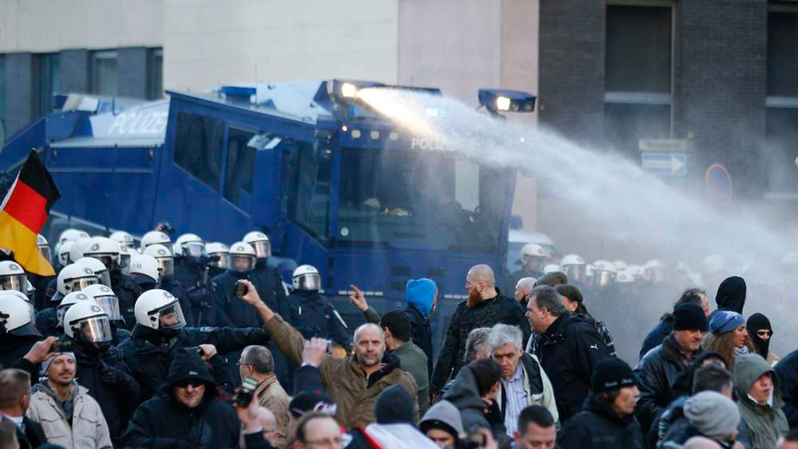 Police use water cannon during protest march by supporters of PEGIDA protest in Cologne