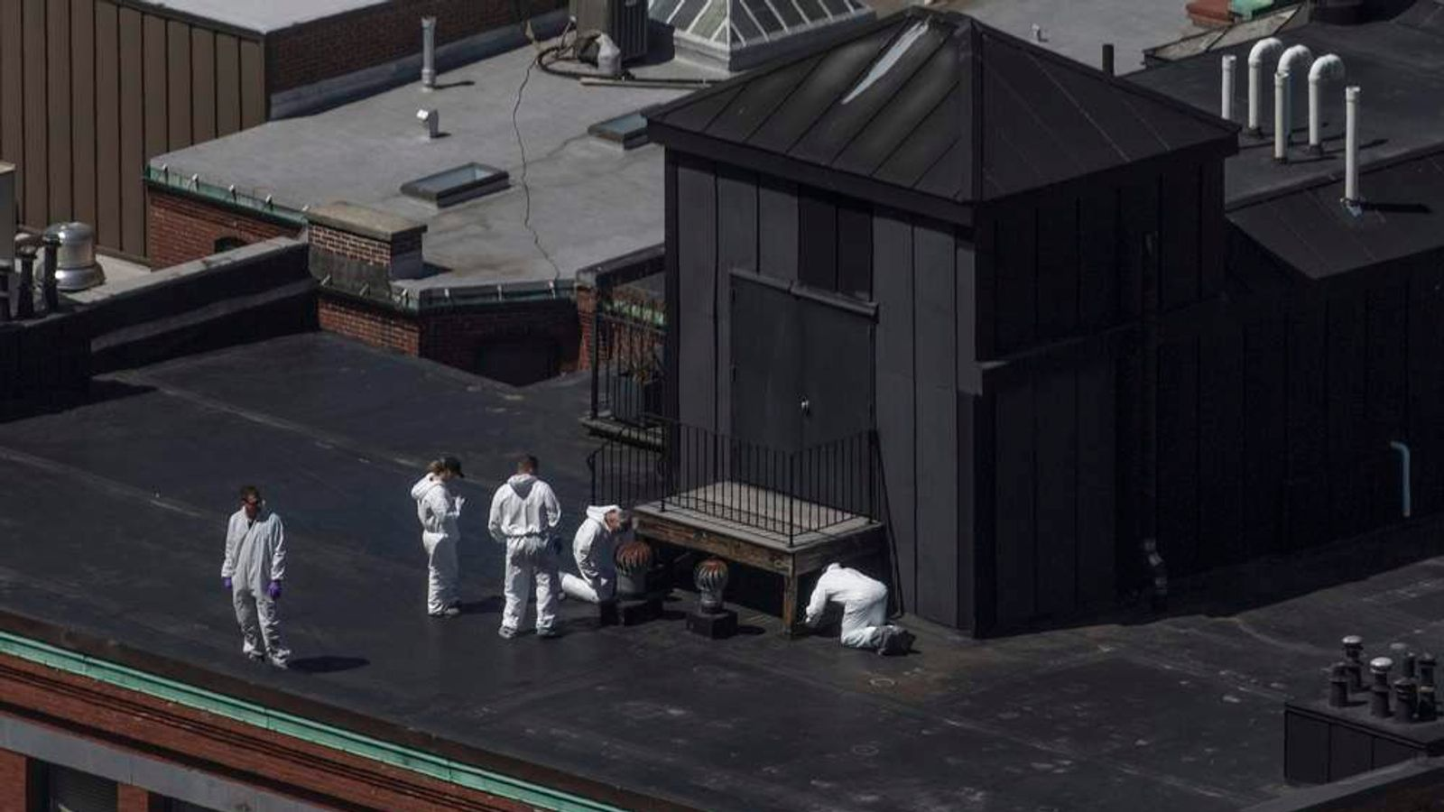 Investigators search for evidence on the rooftop of a building located above the site of a bomb blast on Boylston Street two-days after multiple explosions at the Boston Marathon killed three and injured 176 in Boston