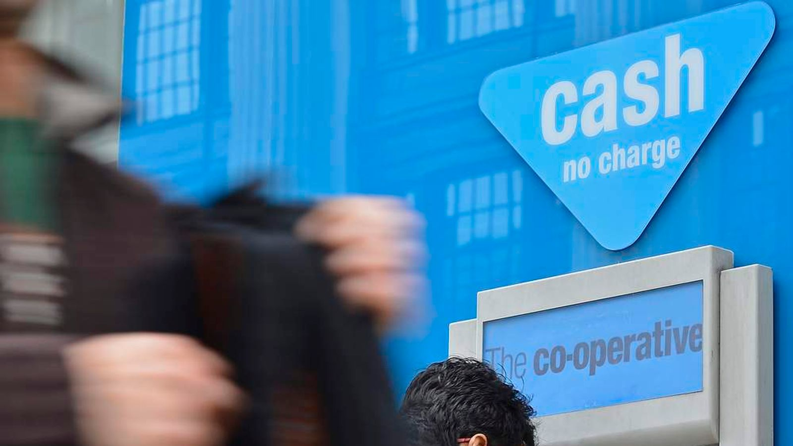 A man uses a cash point machine outside of a branch of the Co-operative Bank in central London