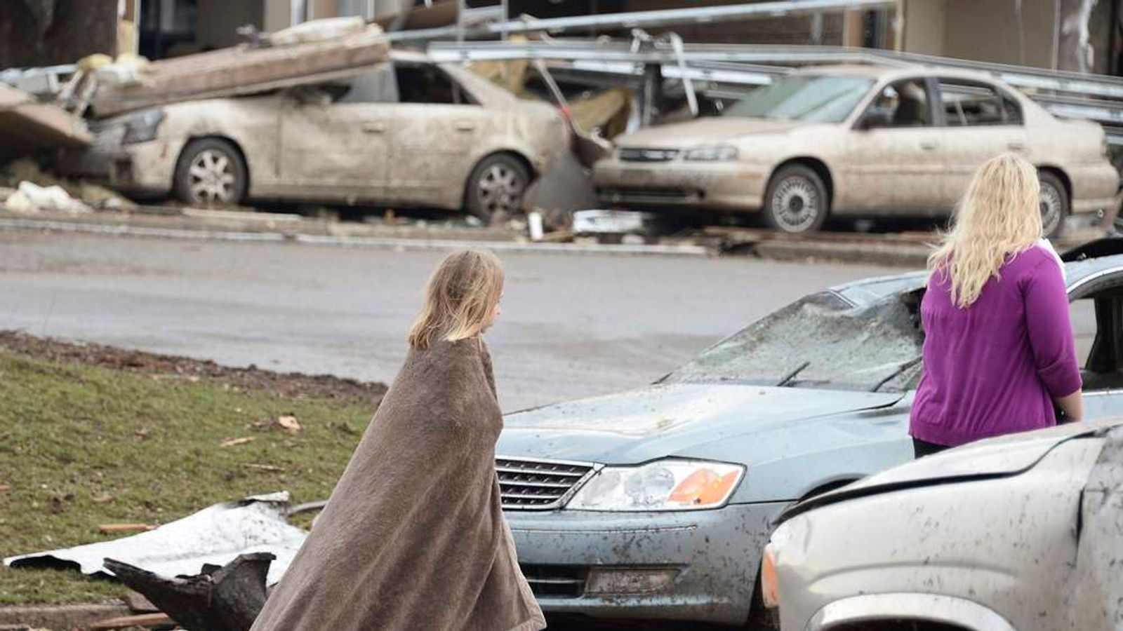 A girl tries to keep warm near the Moore Hospital after being hit tornado that destroyed buildings and overturned cars in Moore