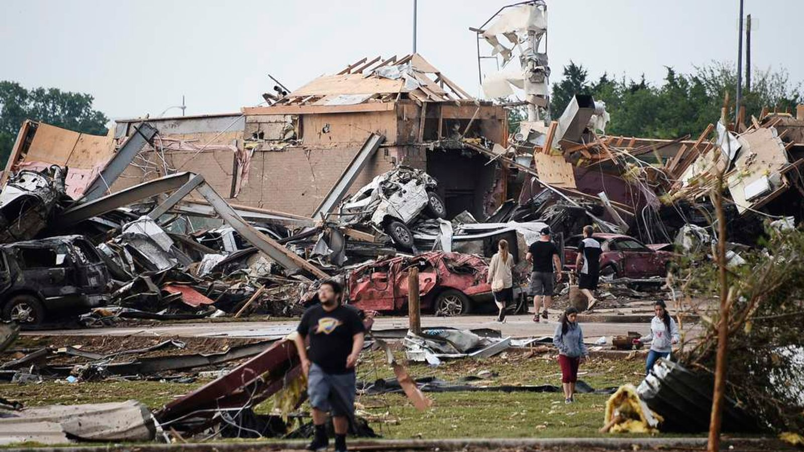 People walk near destroyed buildings and vehicles after a tornado struck Moore