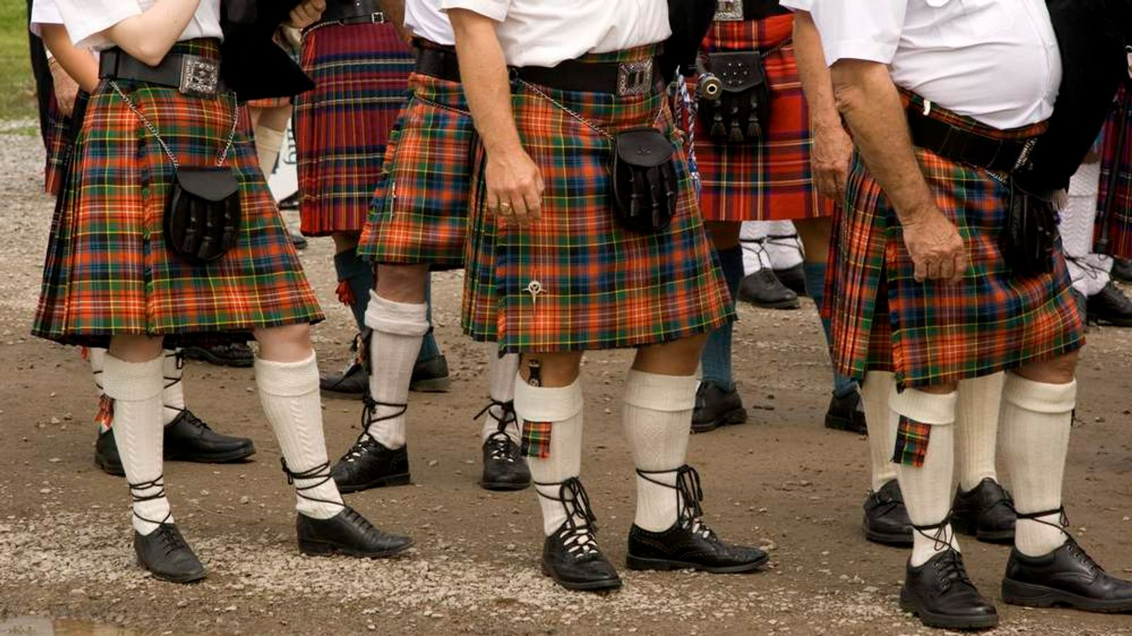 Three Scottish pipers wearing kilts