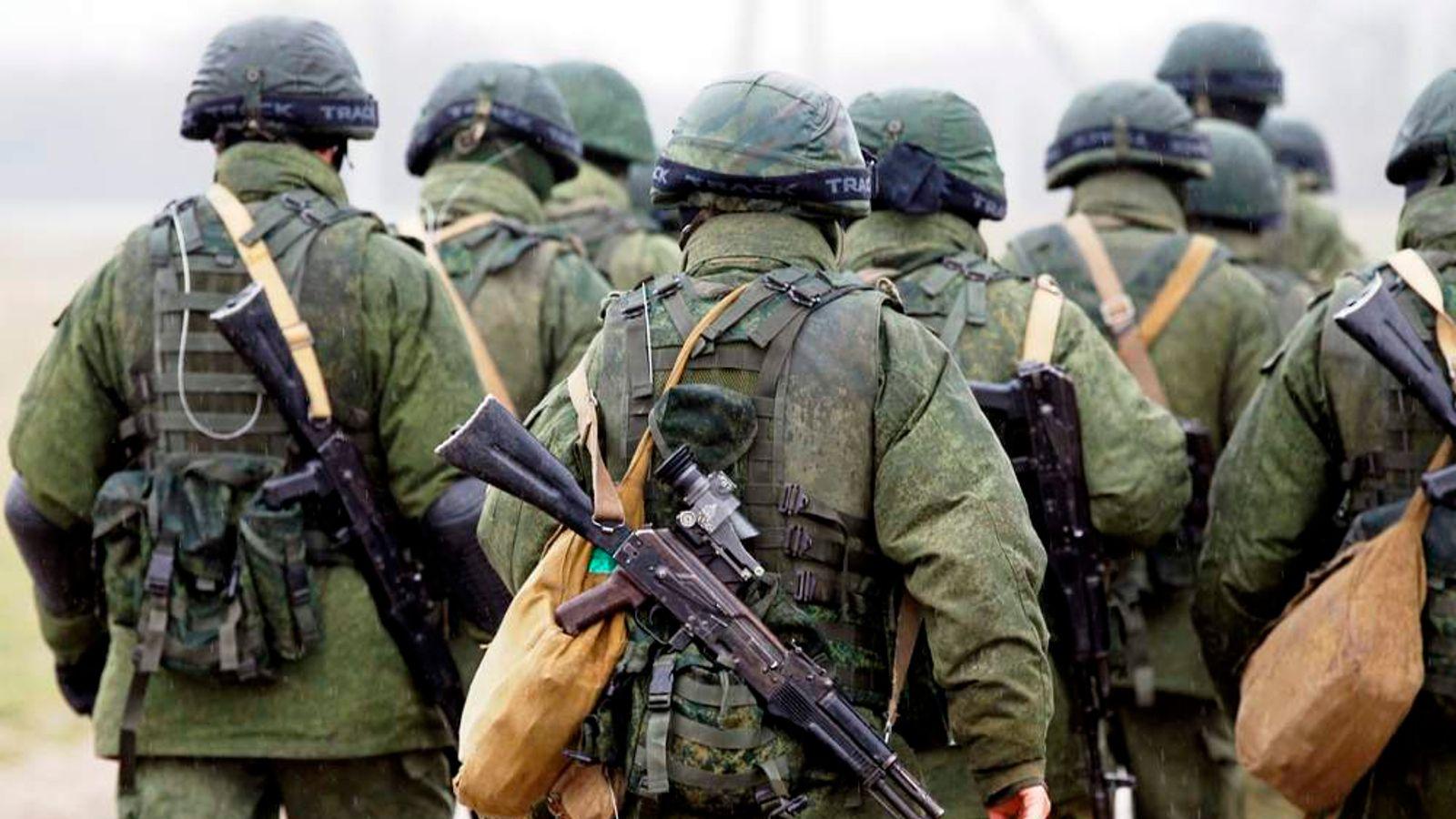 Uniformed men, believed to be Russian servicemen, walk in formation near a Ukrainian military base in the village of Perevalnoye outside Simferopol