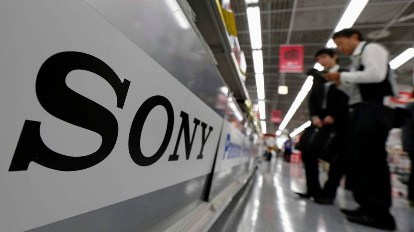 A Sony logo is seen as customers look at Sony's digital cameras at an electronic shop in Tokyo