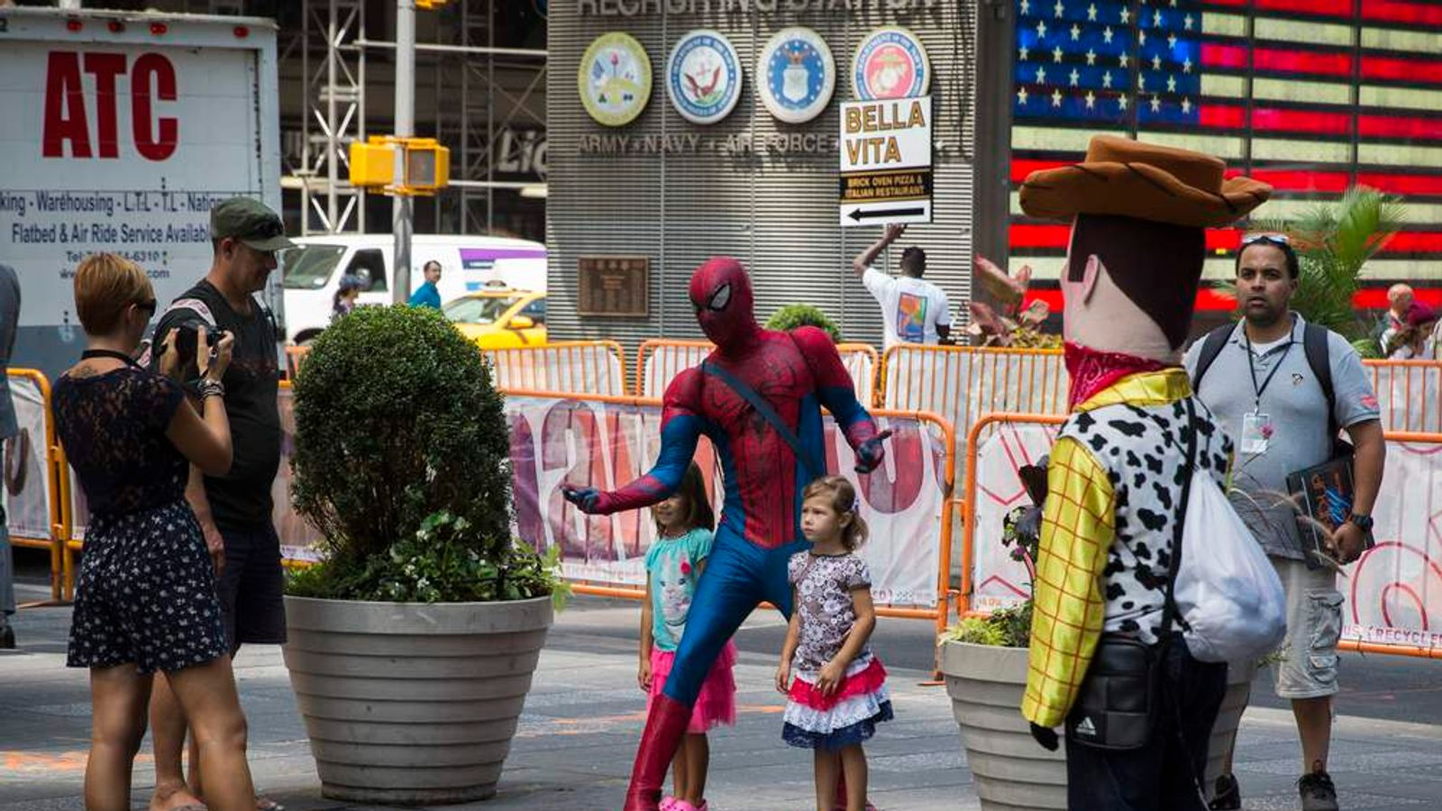 A person dressed in a Spiderman costume stands with children in the Times Square region of New York