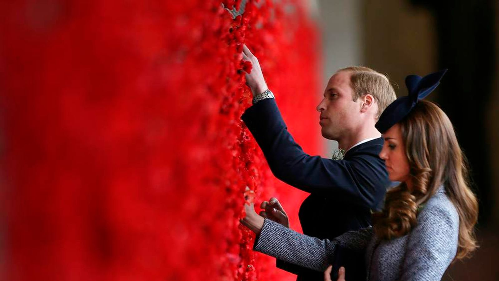 William and Kate place poppy flowers into the World War One Wall of Remembrance in Canberra