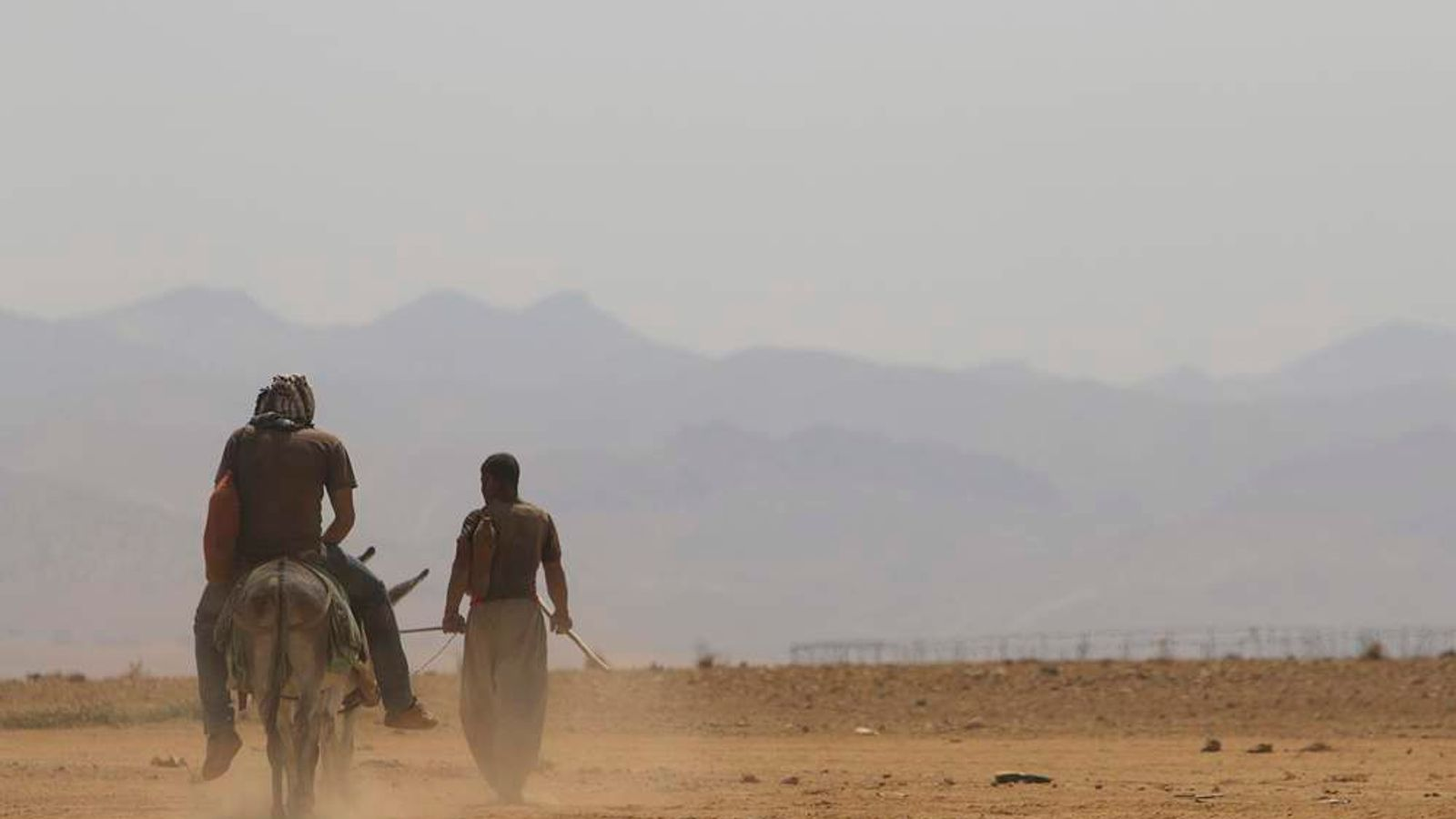 Two Yazidis head towards the Mount Sinjar