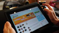 A woman views the Chinese social media site Weibo on a tablet device.