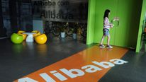 A Chinese Alibaba employee walks through a communal space at the company headquarters in Hangzhou