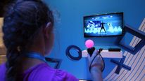 A girl plays a dancing game on a Playstation 3