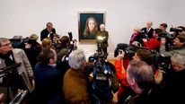 British artist Paul Emsley poses in front of his portrait of Catherine, The Duchess of Cambridge