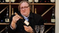 French actor Gerard Depardieu holds a bottle of wine