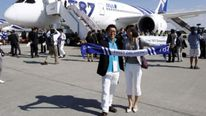 Passengers pose before boarding All Nippon Airways' (ANA) Boeing 787 Dreamliner aircraft