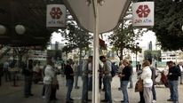 Cypriots and foreigners wait in line to withdraw money from an ATM of a Laiki (Popular) Bank