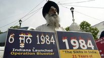 A Sikh activist holds placards during the 24th anniversary of operation Blue Star