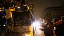 Rioters climb a city bus