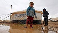 A Syrian refugee boy stands outside his parents' tent after heavy rain at the Al-Zaatari refugee camp in the Jordanian city of Mafraq